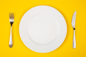 Aerial view of a white plate against a yellow table with a knife and fork